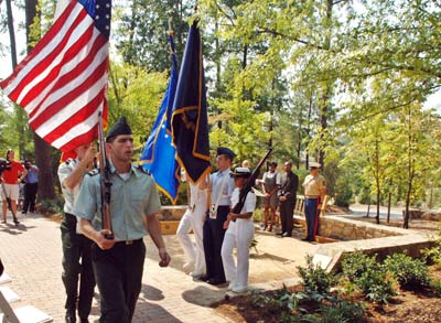 The color guard from UNC's ROTC units leaves the 9/11 Memorial Garden at the close of the dedication ceremony on Tuesday. The rock wall and surrounding plantings define the garden.