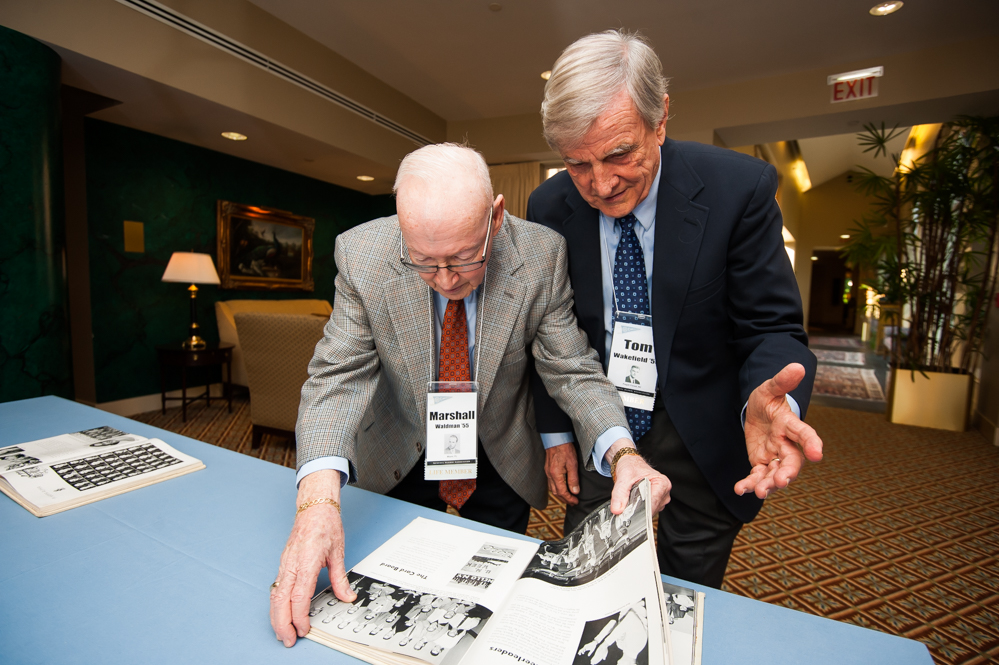 Marshall Waldman '55 and Tom Wakefield '55 look over Yackety Yacks from their class years at Carolina. (Photo by Shane Snider)