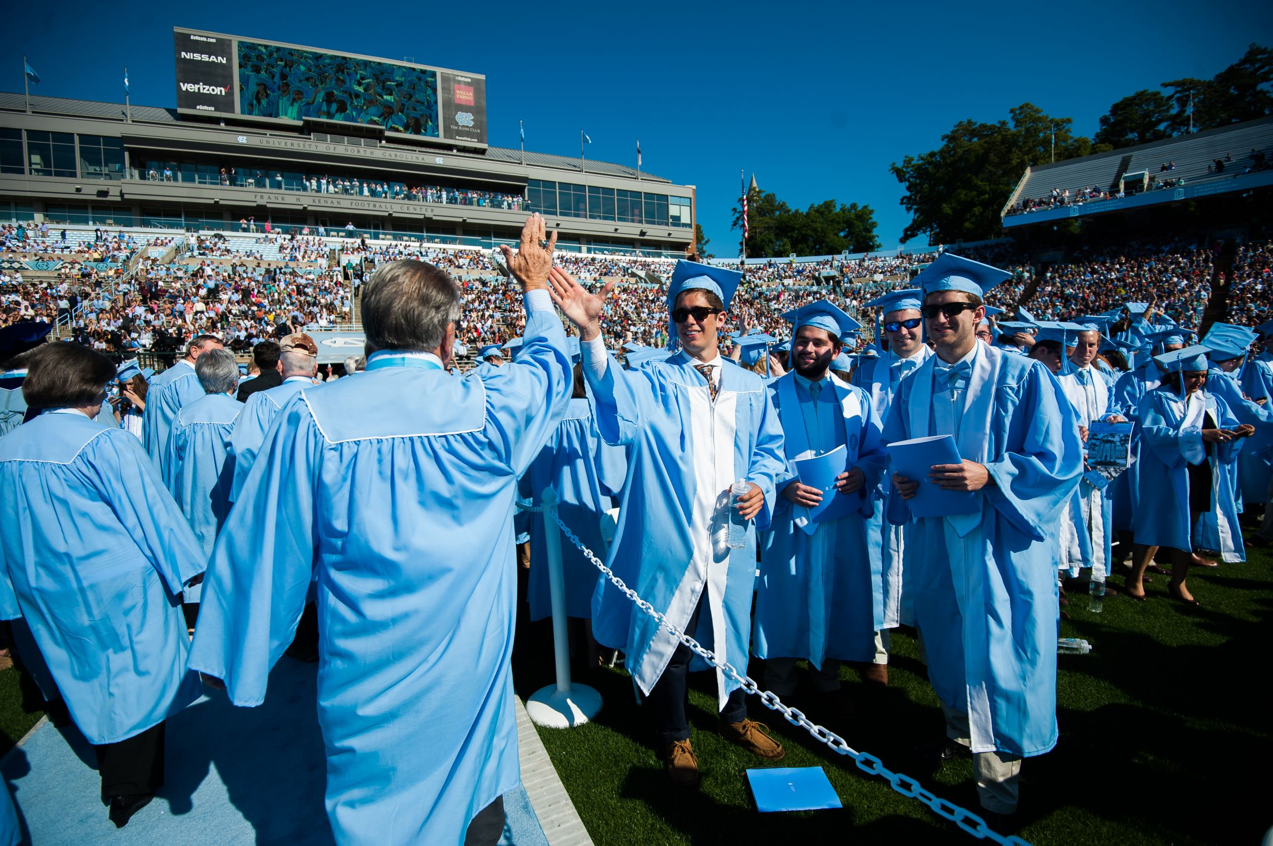 Members of the class of 2017 high-five the alumni as they march in Kenan Stadium. (Photo by Shane Snider)
