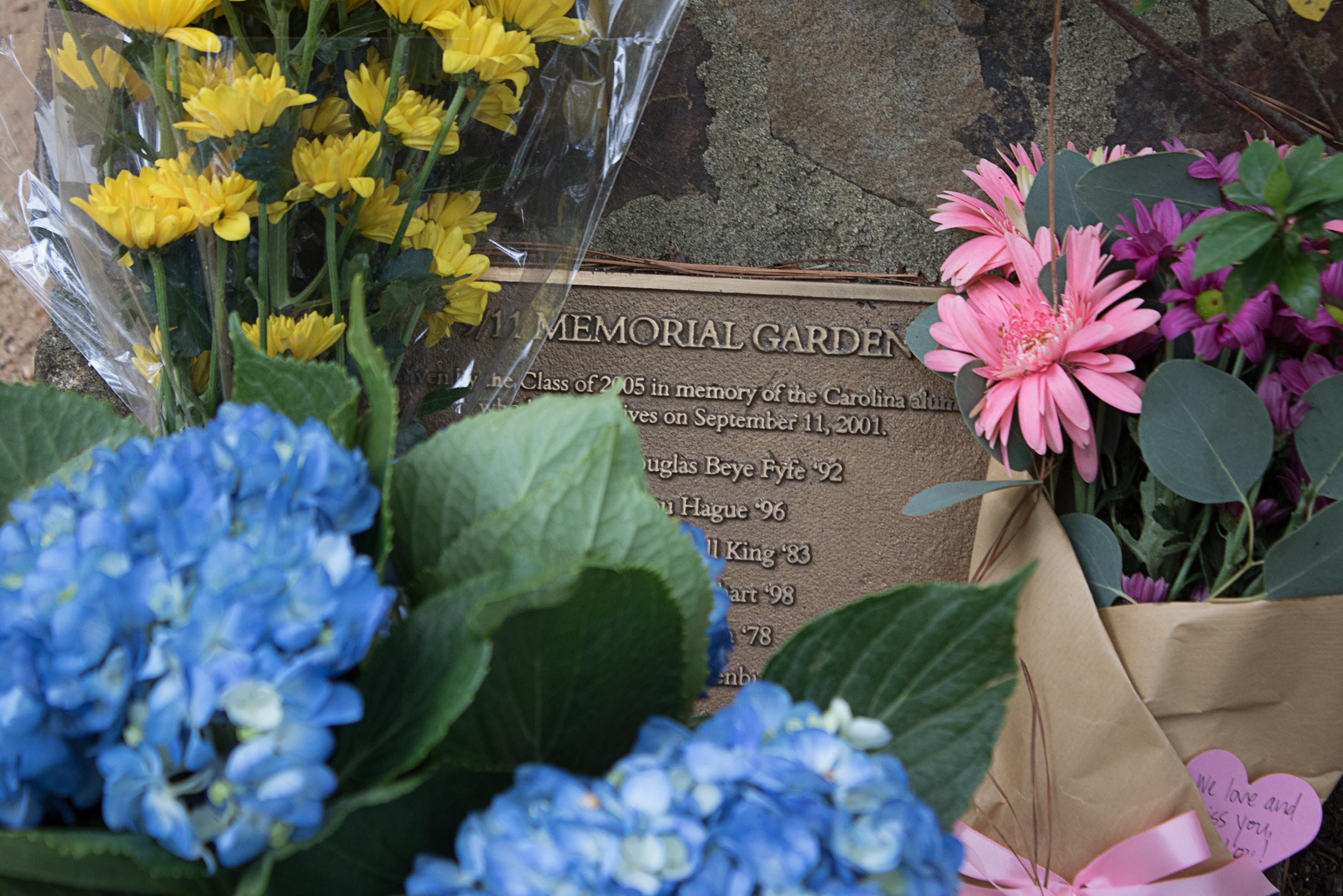 Flowers left at the plaque in the 9/11 Memorial Garden on Stadium Drive near the George Watts Hill Alumni Center. The plaque lists the names of the six alumni lost on 9/11. (Photo by Jason D. Smith '94)